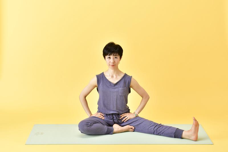 左脚を伸ばして、外側に開く。右脚はかかとを恥骨に合わせるよう、膝を曲げている女性