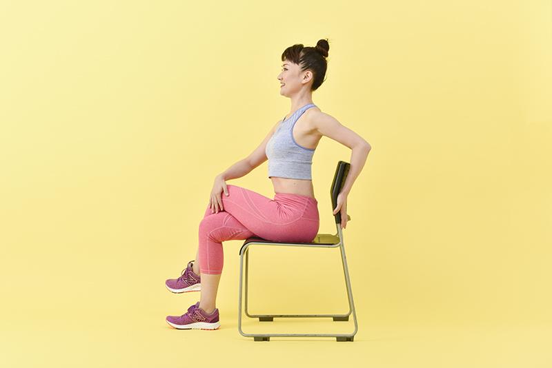 左脚を右脚の太ももにかけて、右手を左脚の太ももに、左手は椅子の背もたれに置く女性