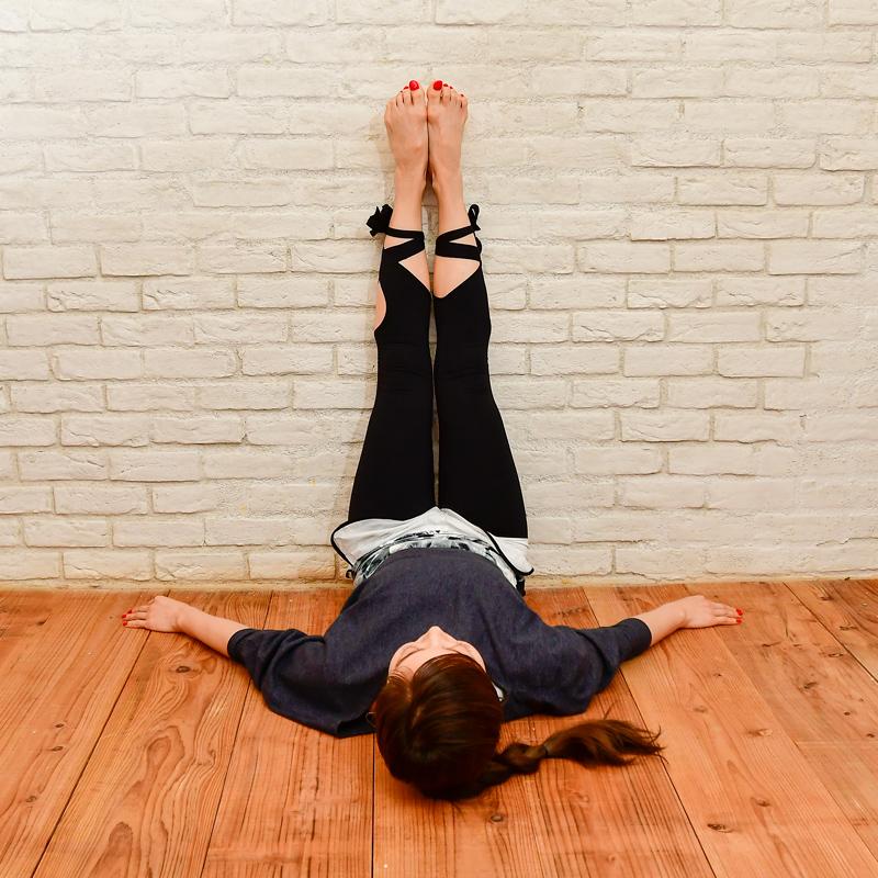 お尻を壁につけたまま、両足を揃えてまっすぐにしている女性