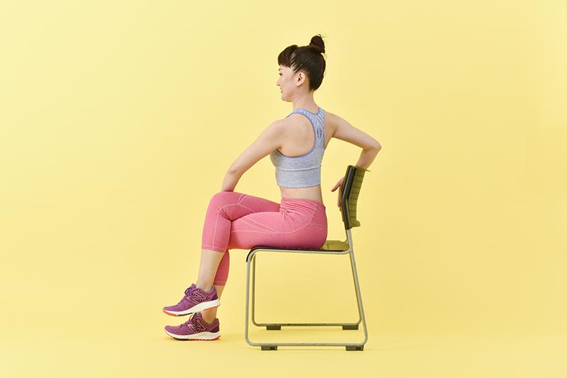 椅子に座った状態で、逆方向に体をねじる女性