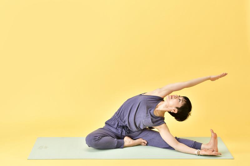 息を吐きながら、左の体側を左の脚に近づけ、二の腕の内側を耳に近づけるように右腕を伸ばす女性