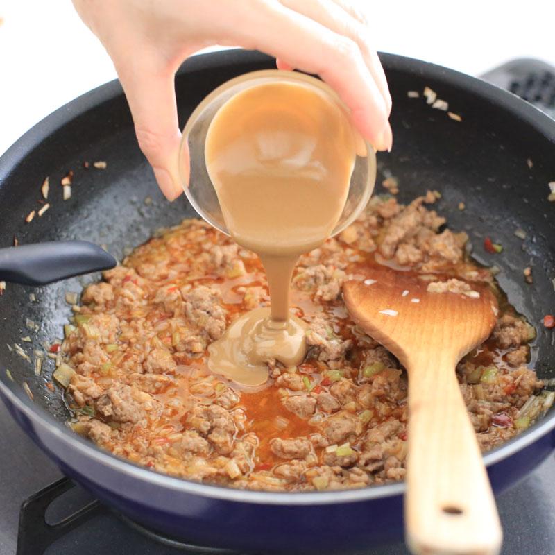 冷やしタンタンを作っている鍋にごまを入れている様子