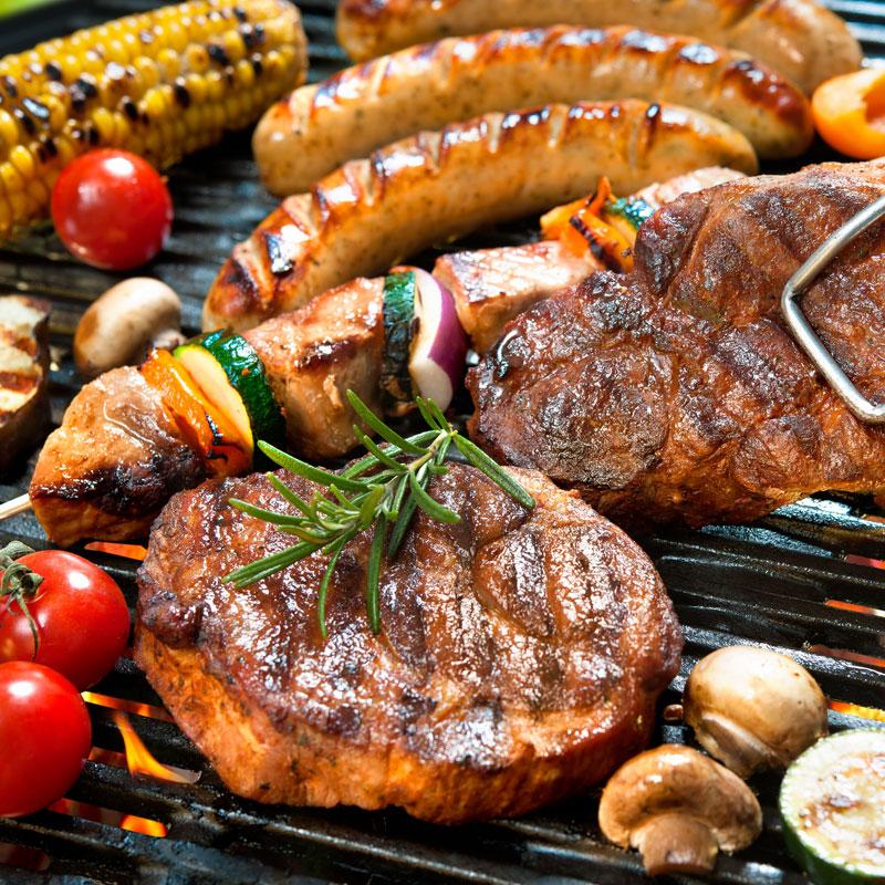 バーベキューで肉、野菜などが焼かれている