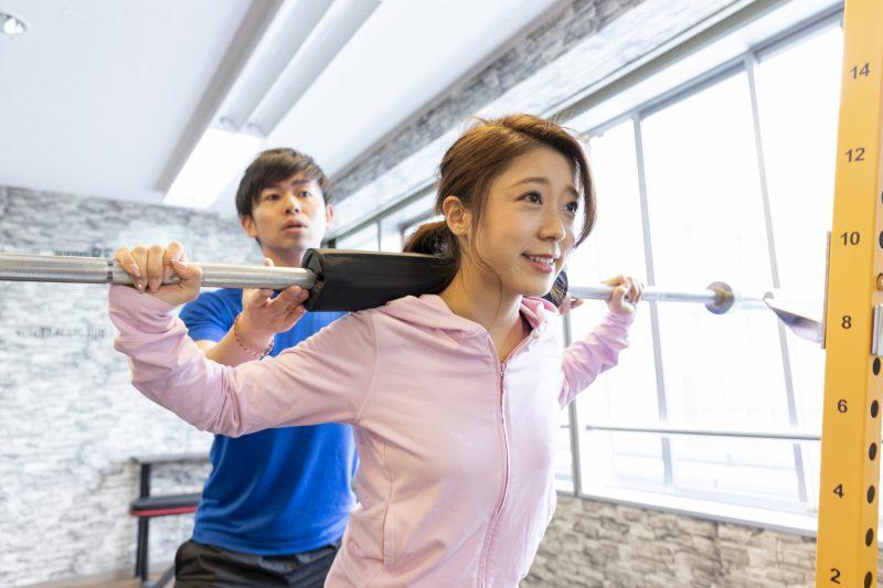 ジムでトレーナーとバーベルを持ち上げる女性