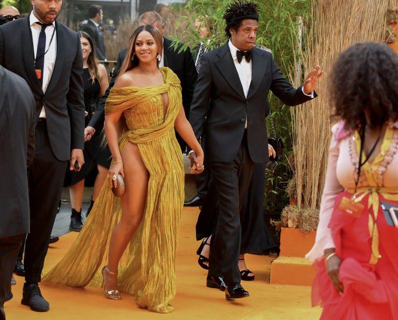ゴールドのドレスを着て笑顔で歩くビヨンセと夫のジェイ・Z