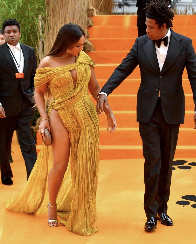 ゴールドのドレスを着て手をつないで歩くビヨンセと夫のジェイ・Z