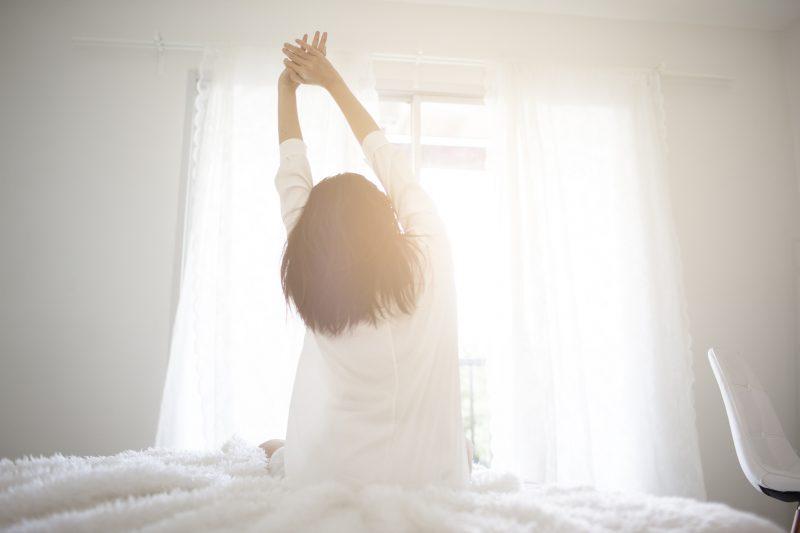 カーテンを開けて朝を迎える女性