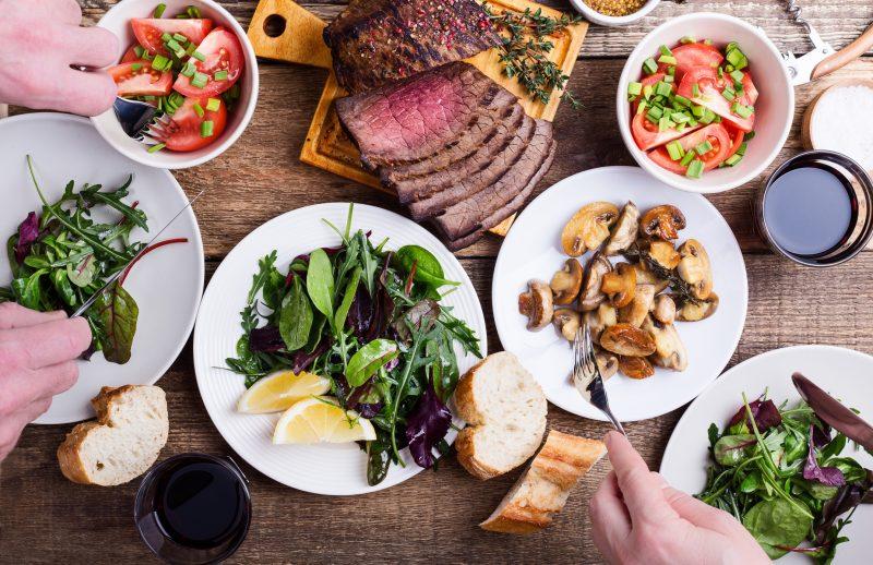 テーブルの上にサラダやきのこ、お肉などが並んでいる