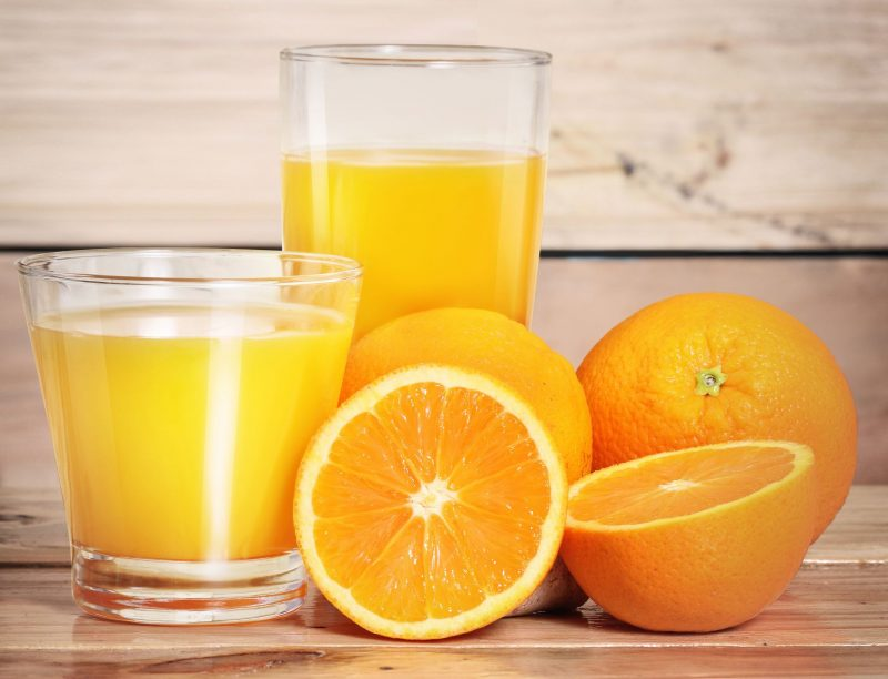 オレンジジュースが入ったグラスとオレンジの実がいくつか並んでいる