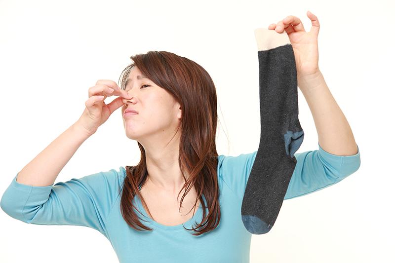 脱いだ靴下を手に、鼻をつまみ臭そうな表情をする女性