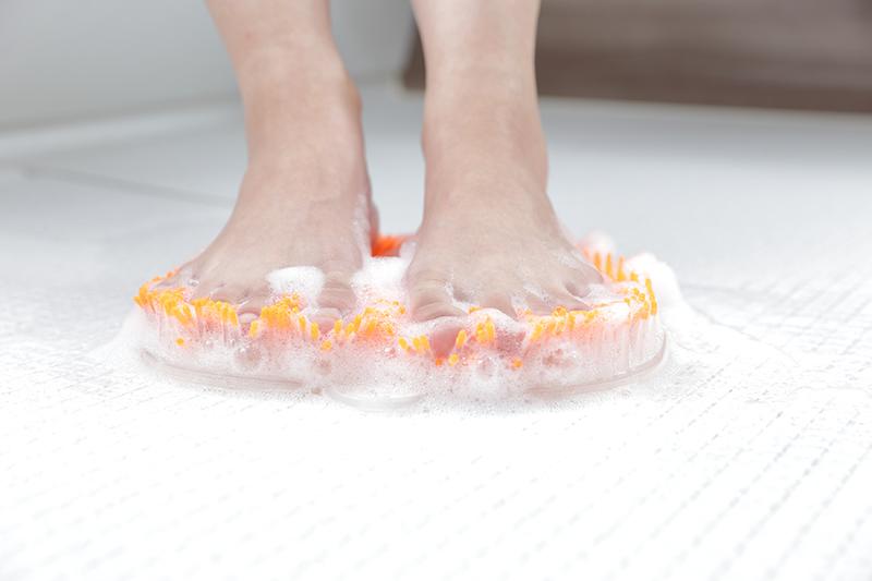 フットグルーマーグランの使用写真。足の裏をたくさんの泡が付いたフットブラシで洗っている