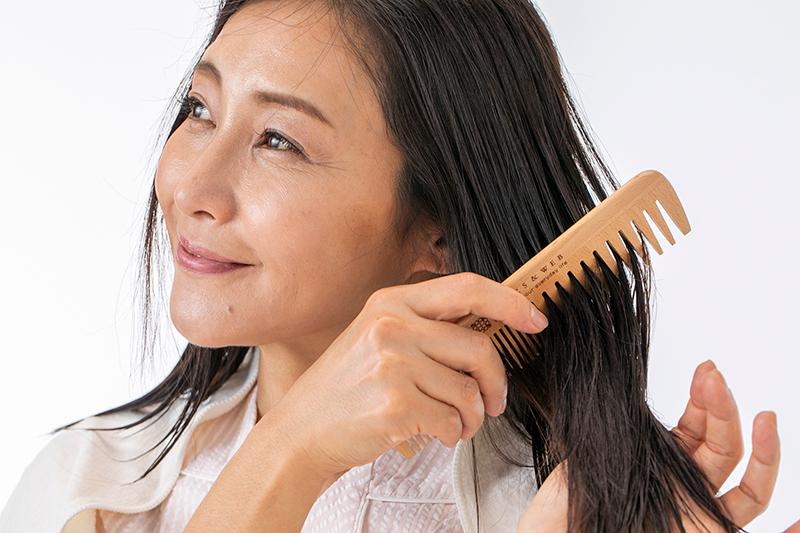 目の粗いコームで濡れた髪をとかす女性