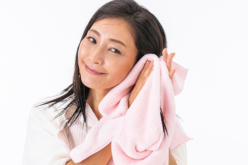 塗れた髪をタオルではさむ女性