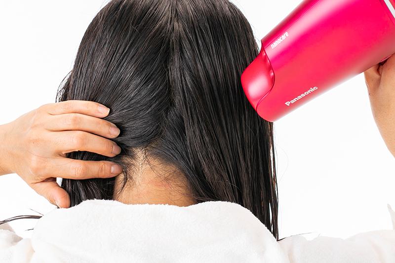 後頭部の根元をドライヤーで乾かす女性