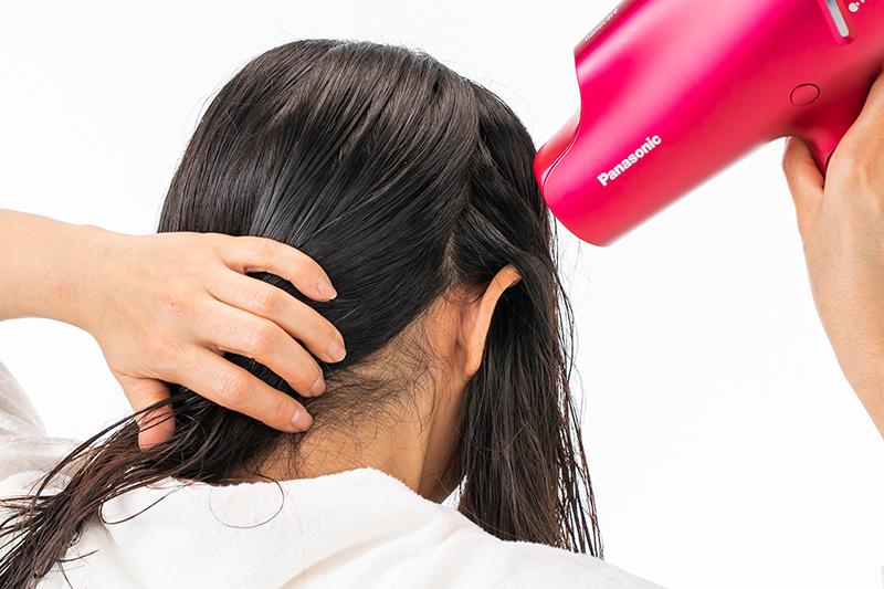 耳の後ろの濡れ髪を乾かす女性