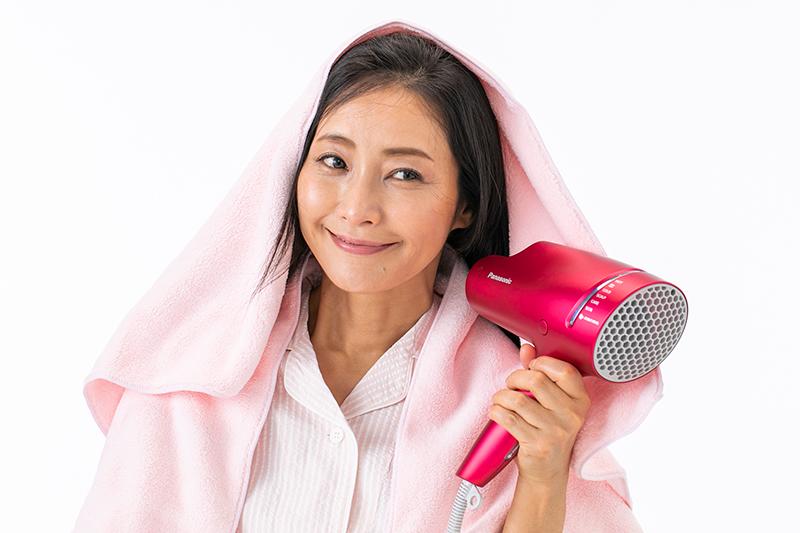 頭にタオルをかけドライヤーで乾かす女性