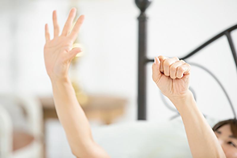 ベッドで横になりながら右手をパー、左手をグーにする女性