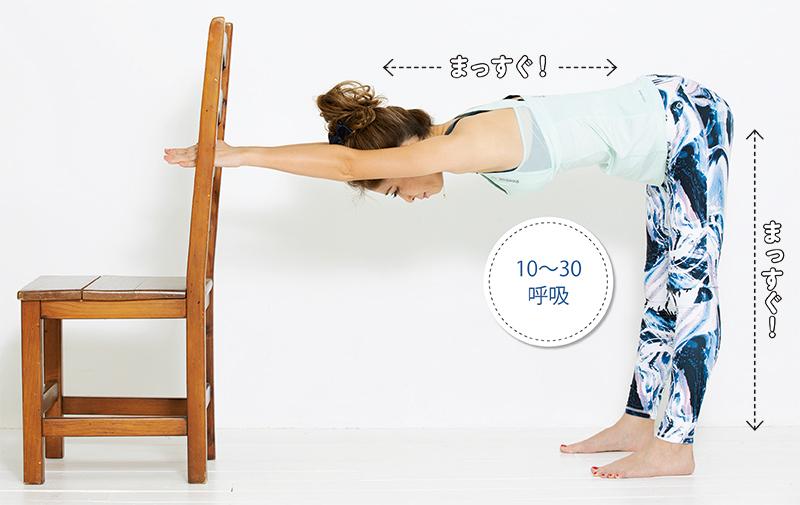 足は肩幅に開き上体を90度に倒し、椅子の背に手をかけた女性の画像