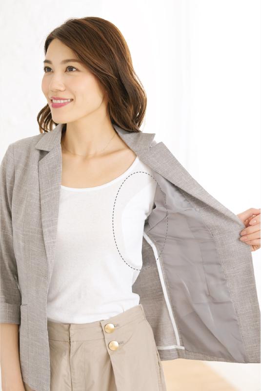 ジャケットを開いてインナーのTシャツを見せる女性
