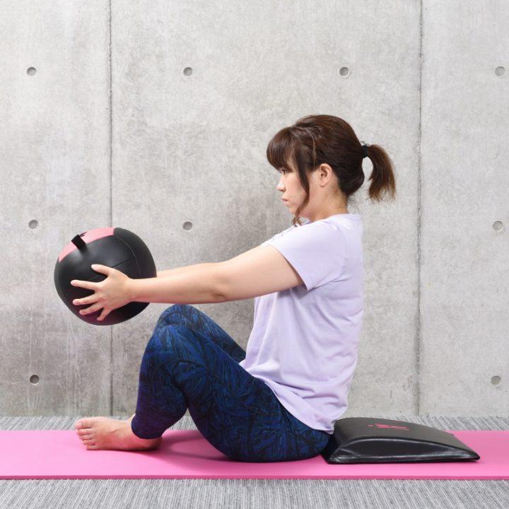 Abマットの上でメッドボールを持ち腹筋をしようとしている女性