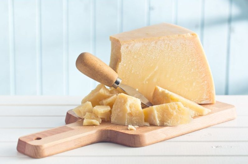 カッティングボードに乗せた大きなパルメザンチーズのかたまり