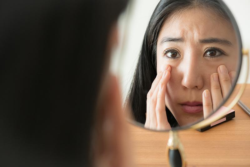 シミを気にして鏡を見る女性