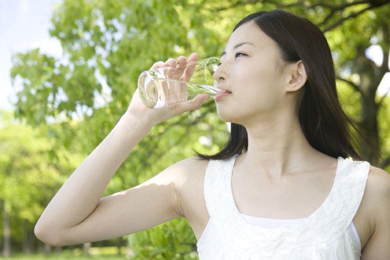 コップの水を飲む日本人女性