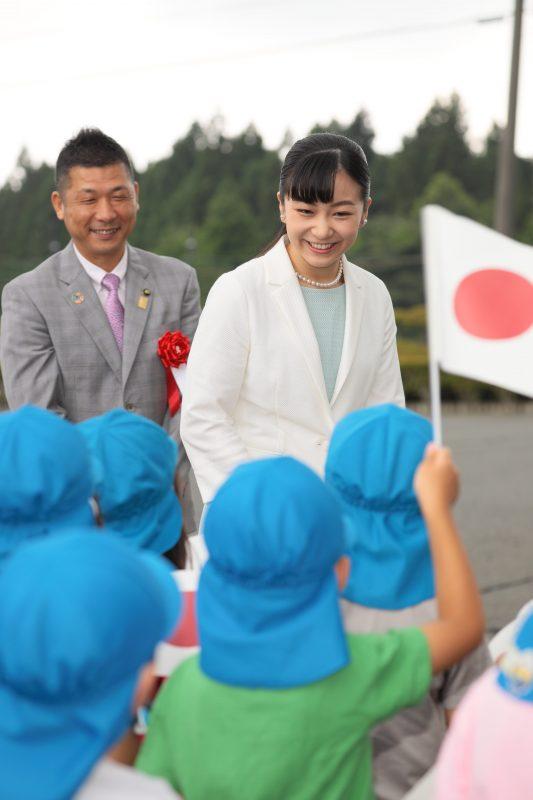2019年7月24日に、アイスブルーのワンピースに白いジャケットをお召しになり馬術競技大会に出席された佳子さま。出迎えた園児に笑顔でお応えする。