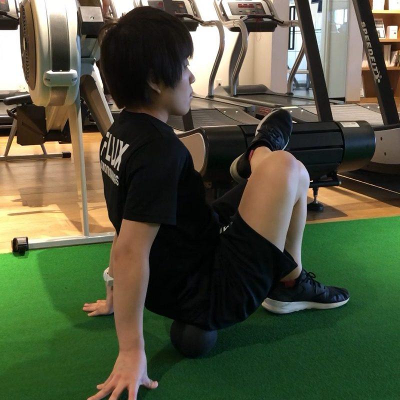 パフォームベタージャパンのファームマッサージボールの使用例としてお尻周りのコリをほぐしている男性