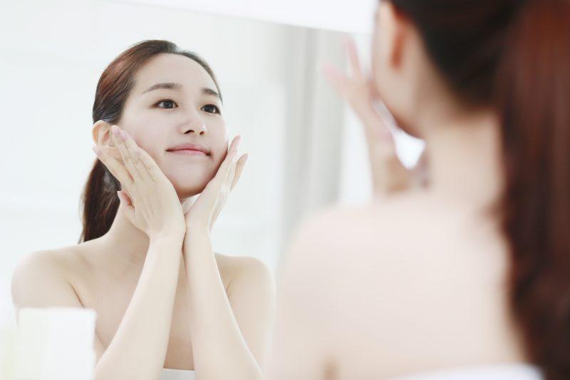 鏡の前でスキンケアをする女性