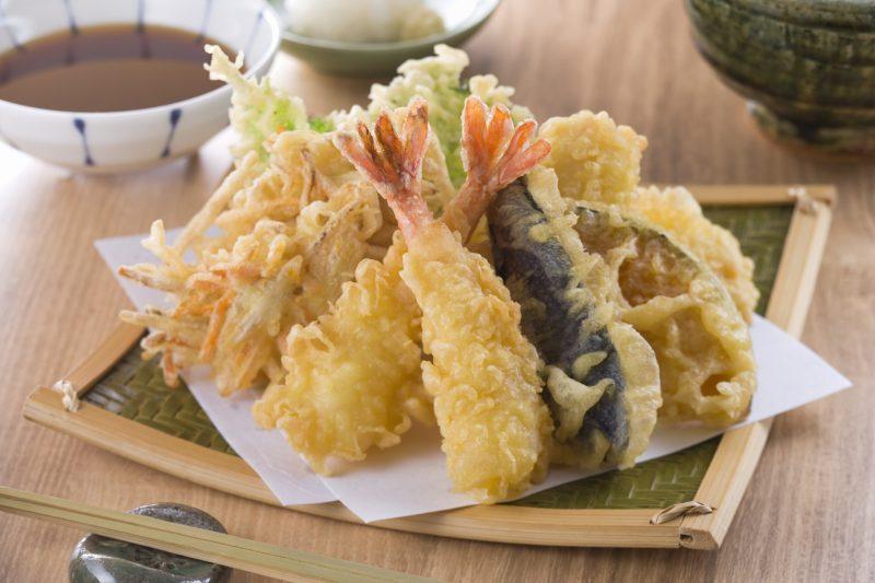 エビや野菜、かき揚げなどの天ぷらが皿に盛りつけられている
