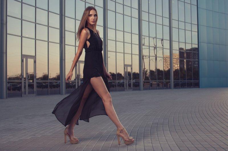 高いヒールのサンダルを履いて歩くブラックのミニドレス姿の女性