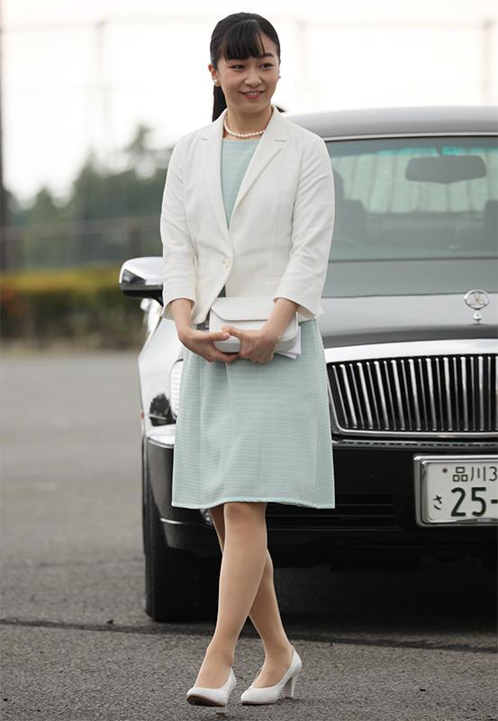 ミントグリーンのワンピースに白のジャケットを羽織って車の前に立たれる佳子さま