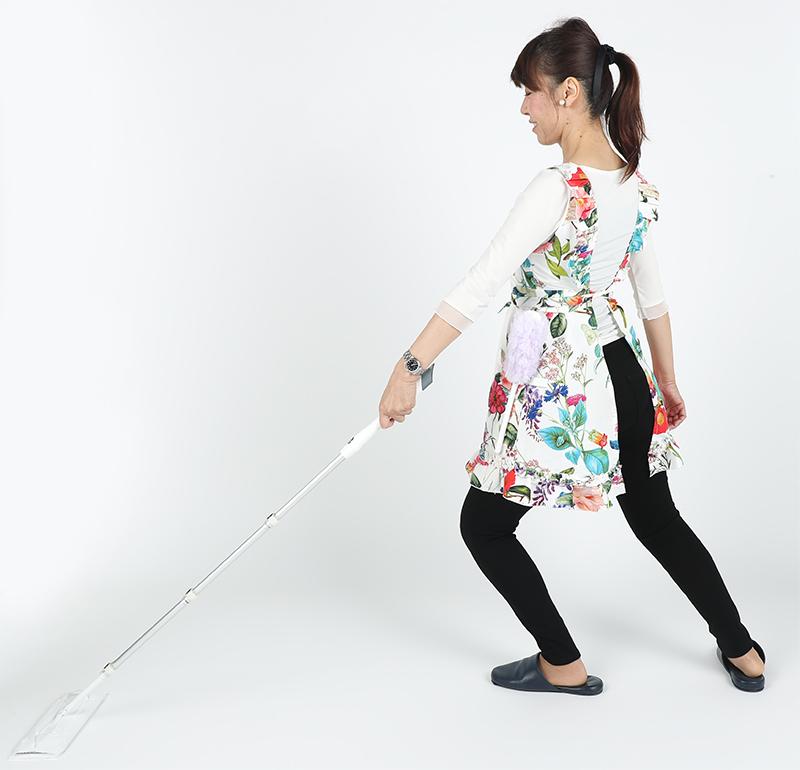 体重を前足にかけながら腕をしっかり伸ばし、片手でモップがけする女性