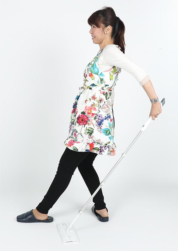 後ろ足に体重を移動させながら、腕を後ろに引いた姿勢でモップをかける女性