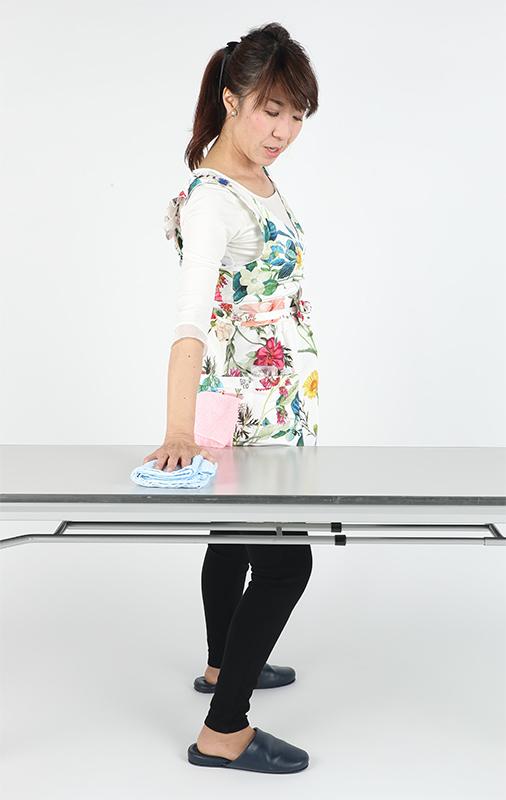 足は肩幅に開き、テーブル側の足を少し前に出して平行に立つ。ウエストを意識し前後にひねりながら濡れ台ふきんで拭く。