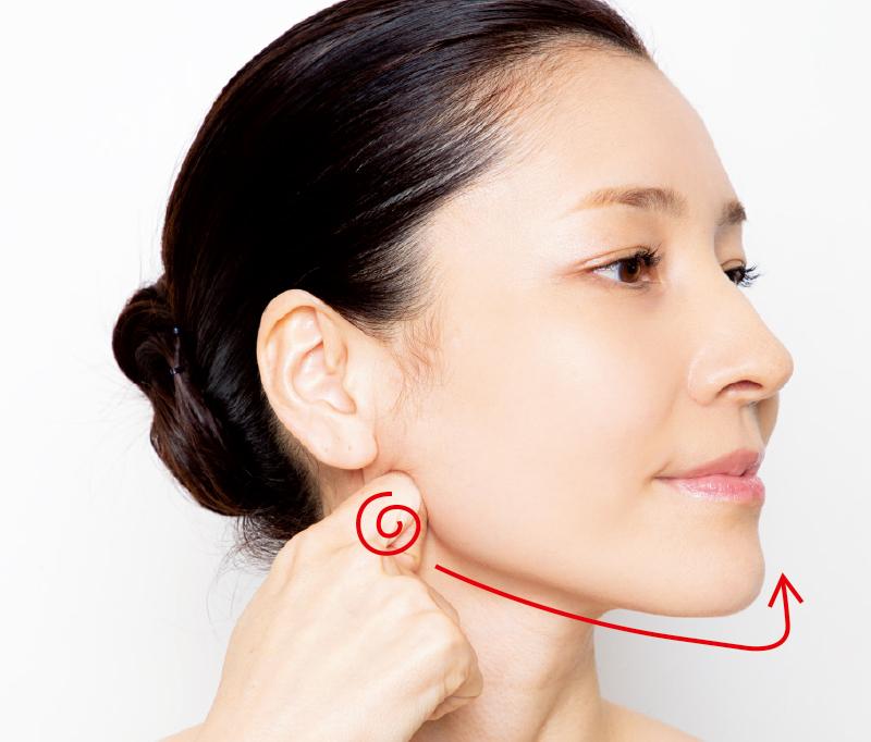 かぎ状にした人差し指を耳の下に添えた女性の横顔画像