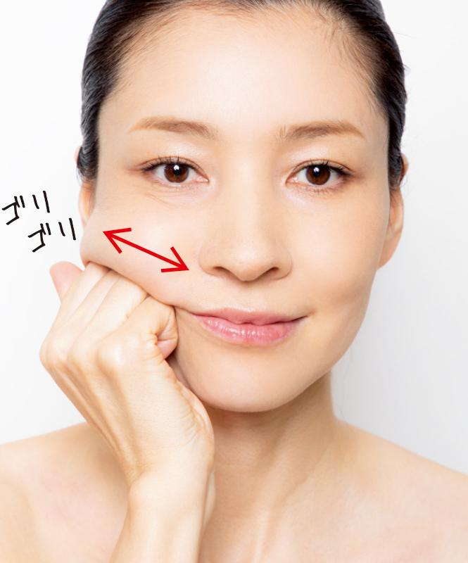 奥歯上の凹みを親指以外の4本の指で小刻みにもみほぐす女性の顔の画像