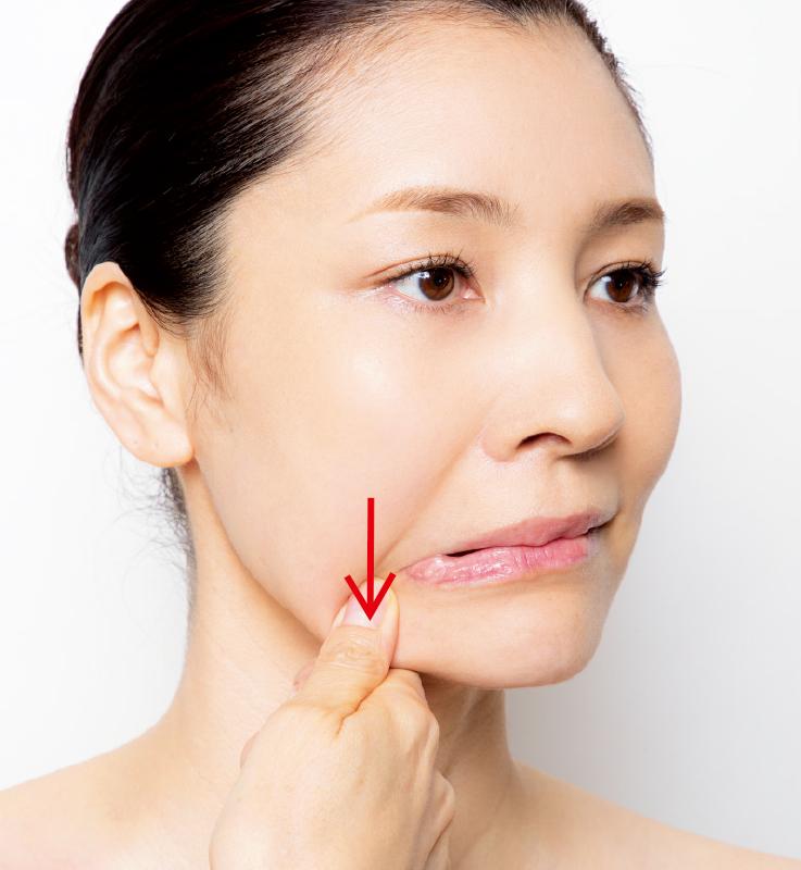 口角から下に伸びるラインに親指を置き親指で押しながら下げる女性の顔の画像