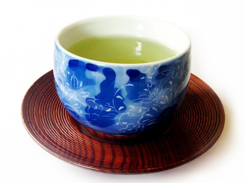 茶托に乗せた緑茶の入った湯飲み写真
