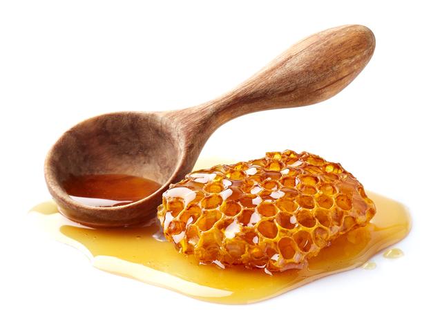 はちみつがスプーンに入っていて、その隣にはちみつに漬かったハチの巣置いてある