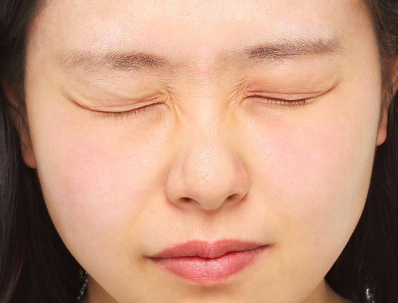 ギューッと目をつぶった女性の画像