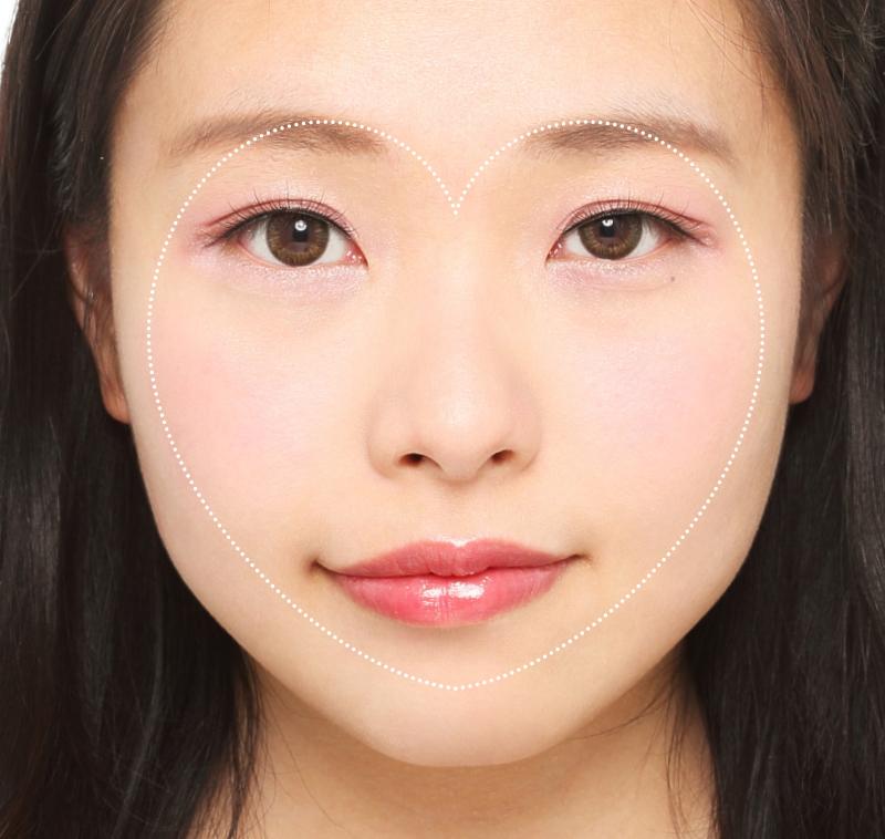 メイクした女性の顔の中にハートを描いた画像