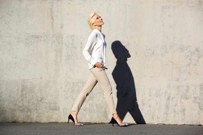 白シャツを着て歩く金髪の女性