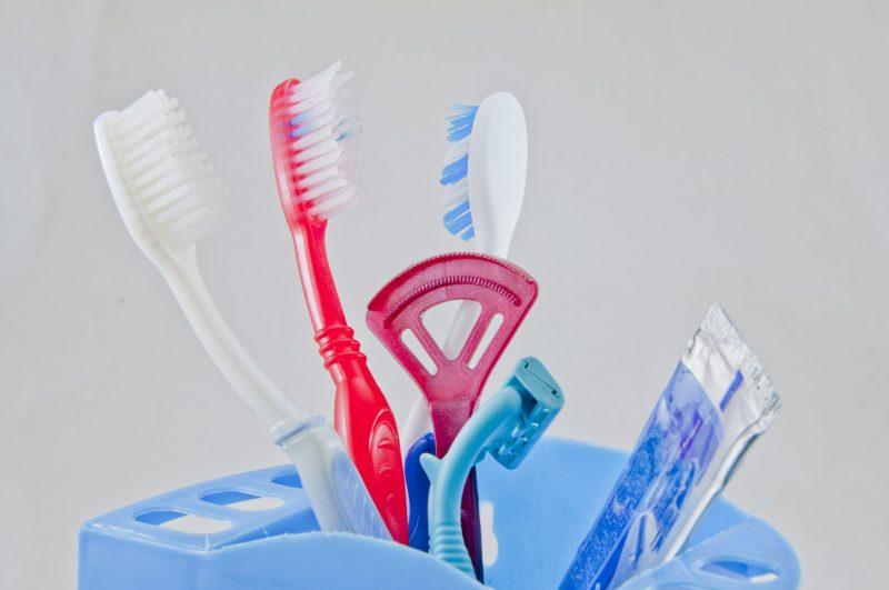 ケースに立てかけられた歯ブラシや舌磨き、歯磨き粉の写真