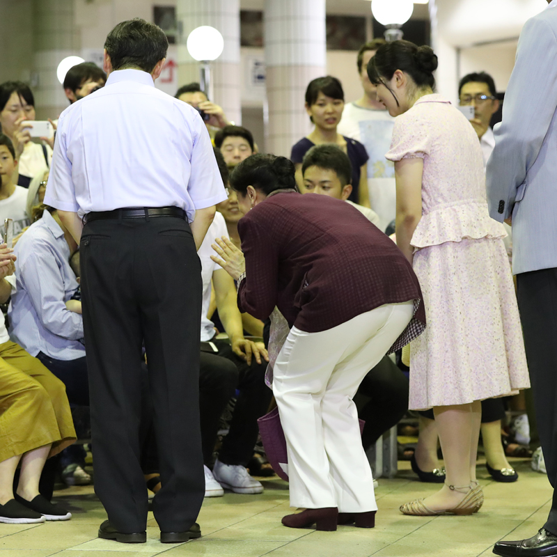 腰を低く、手を振りながらお話される雅子さま。両脇に佇む陛下と愛子さま