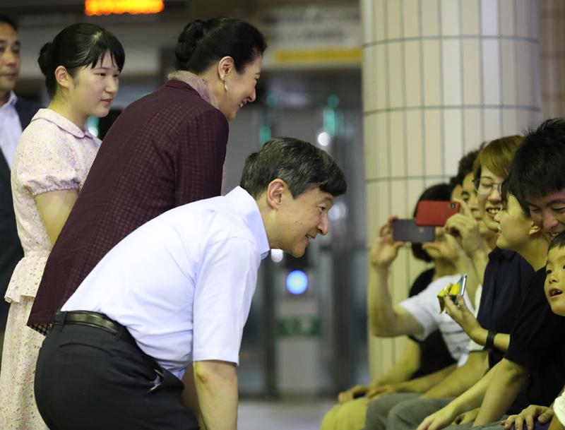 かがみ込んで座る市民と目線を合わせてお話される天皇陛下、スマホカメラに笑顔を向ける雅子さま、おそばで静かに見つめる愛子さま
