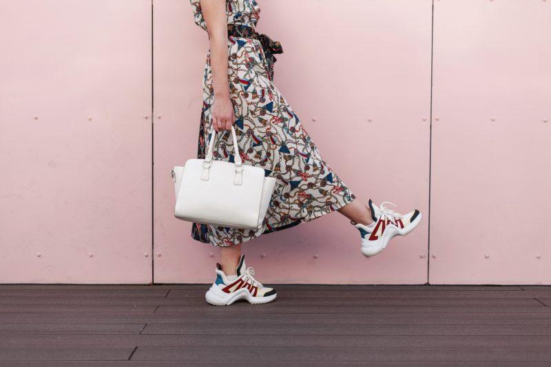 ワンピースに白いレザーバッグ、ハイテクスニーカーを履いた女性