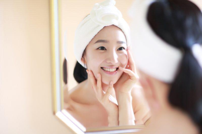 鏡の前でスキンケアをして笑顔の女性