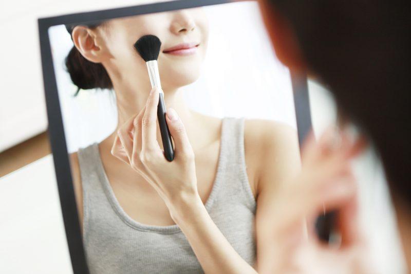 鏡の前でメイクブラシでメイクしている女性